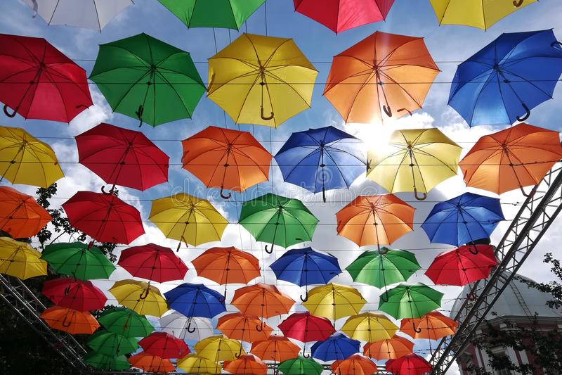 Många kulöra paraplyer på bakgrund för blå himmel arkivfoto