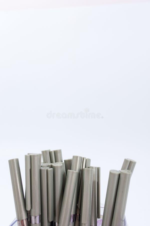 Många kulspetspennor på en vit bakgrund arkivbild