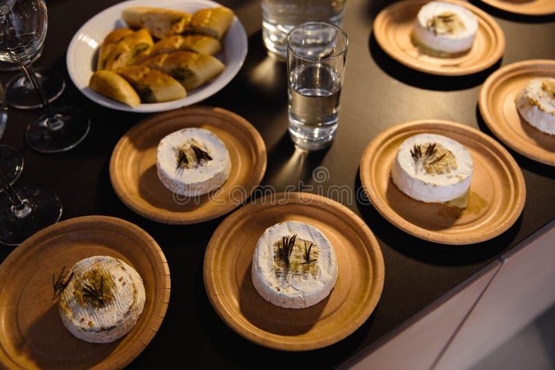 Många läckra varma bakade camemberts med sultaninnor och rosmarin på en tabell arkivfoton