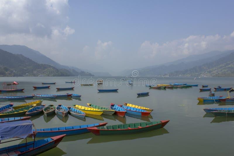 Många ljusa mångfärgade tomma träfartyg på Phewa sjön på bakgrunden av en grön bergdal i ogenomskinligheten royaltyfria foton