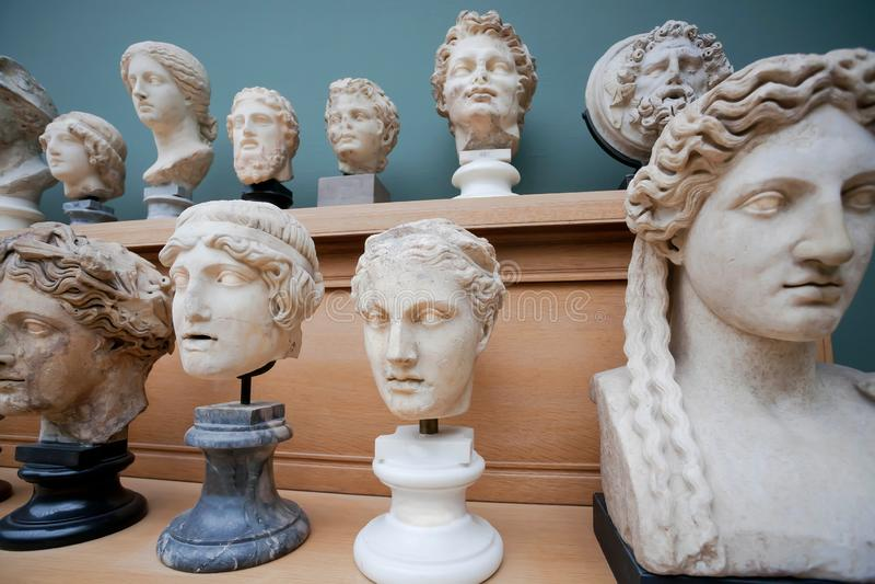 Många mänsklig framsida- och marmorhuvudkopior av gamla romerska gudar och kejsare på hylla Minnen om människa av den forntida vä royaltyfria bilder