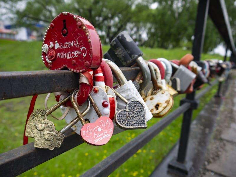 Många mång--färgade hänglås på bron arkivbild