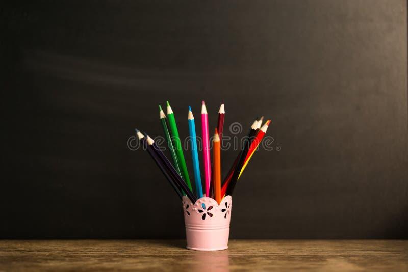 Många mångfärgade blyertspennor i exponeringsglas på trätabellen med svart bakgrund tillbaka begreppsskola till arkivbild