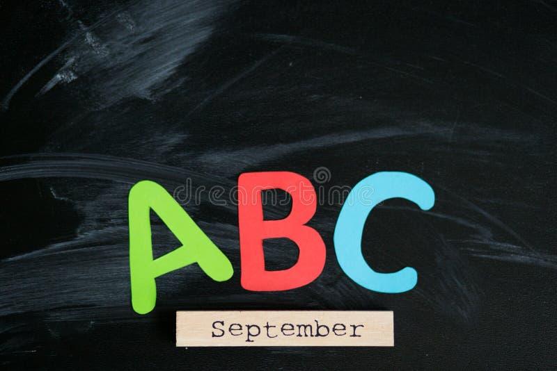Många mångfärgade bokstäver på svart tavla arkivfoton