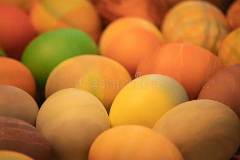 Många mångfärgade kokta ägg med olika modeller som dekoreras och färgas för easter arkivfoton