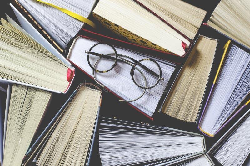 Många mångfärgade tjocka öppna böcker står på en mörk bakgrund På böckerna är gamla runda exponeringsglas och en öppen anteckning fotografering för bildbyråer