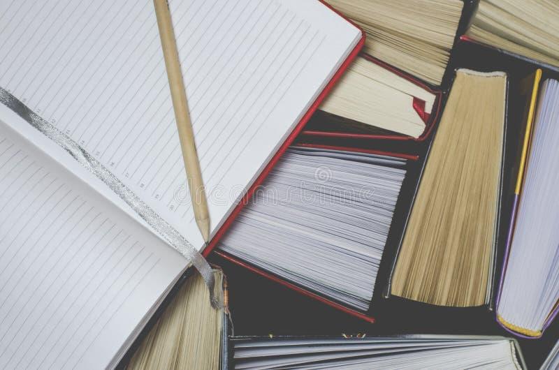 Många mångfärgade tjocka öppna böcker står på en mörk bakgrund På böckerna är gamla runda exponeringsglas och en öppen anteckning arkivbilder