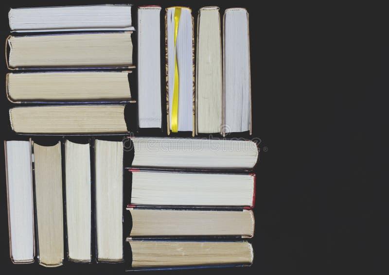 Många mångfärgade tjocka öppna böcker står på en mörk bakgrund På böckerna är gamla runda exponeringsglas och en öppen anteckning royaltyfri bild