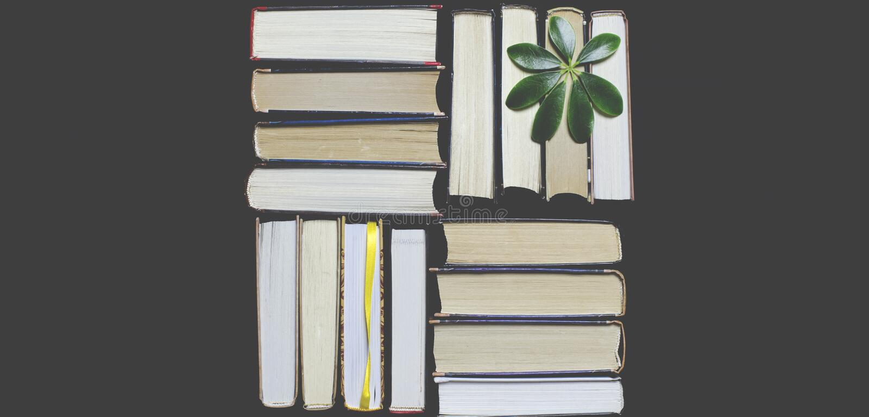 Många mångfärgade tjocka öppna böcker står på en mörk bakgrund På böckerna är gamla runda exponeringsglas och en öppen anteckning royaltyfri fotografi