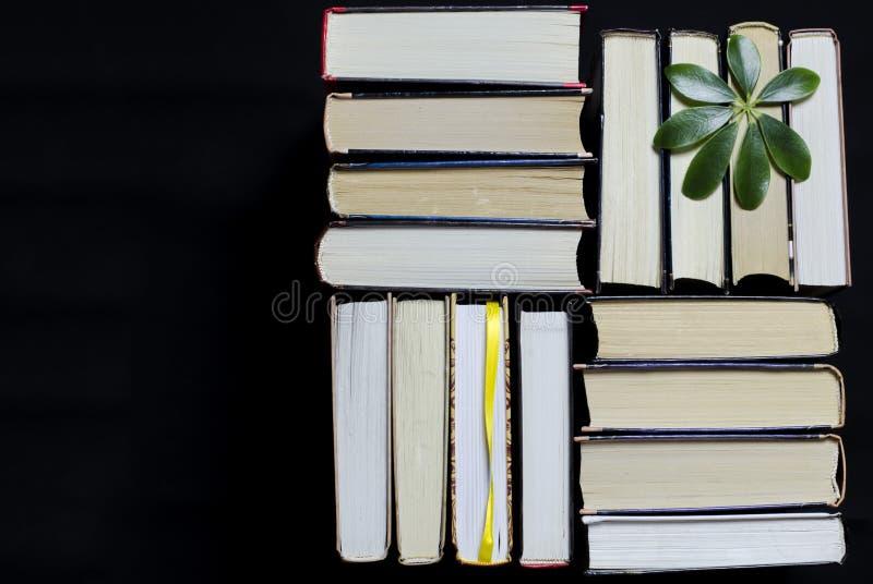 Många mångfärgade tjocka öppna böcker står på en mörk bakgrund På böckerna är gamla runda exponeringsglas och en öppen anteckning arkivbild