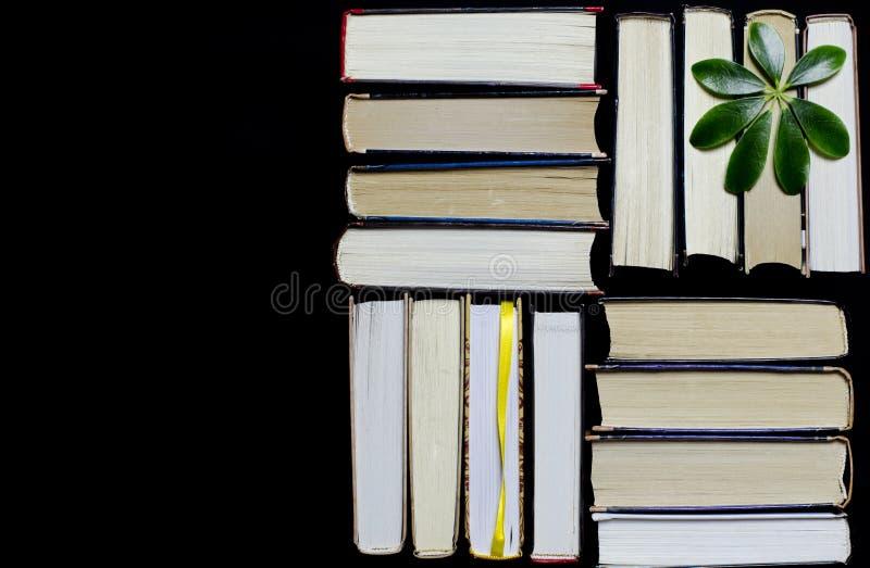 Många mångfärgade tjocka öppna böcker står på en mörk bakgrund På böckerna är gamla runda exponeringsglas och en öppen anteckning royaltyfri foto