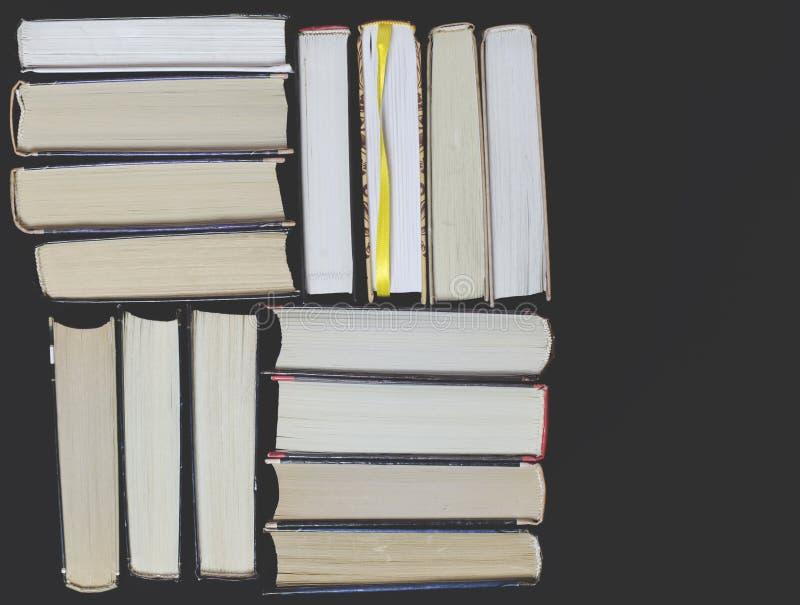 Många mångfärgade tjocka öppna böcker står på en mörk bakgrund På böckerna är gamla runda exponeringsglas och en öppen anteckning royaltyfria bilder