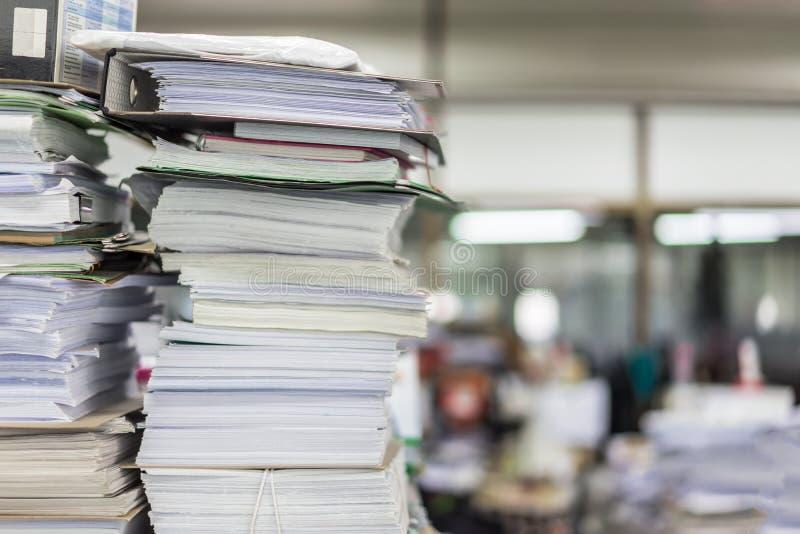 Många mappar och högar av papper lägger på en smutsig kontorstabell royaltyfri bild