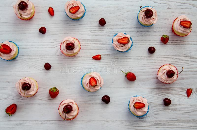 Många muffin med vita kräm och jordgubbar på en trätabell royaltyfria foton