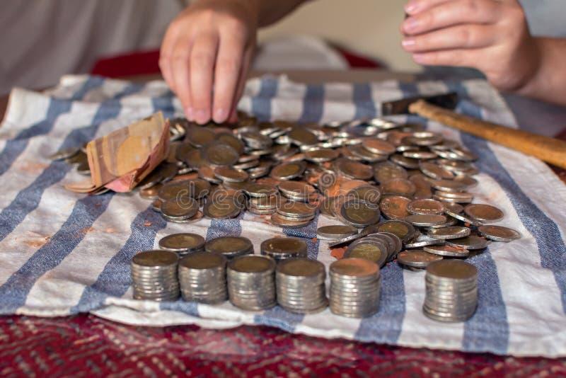 Många mynt från en spargris och två händer som väljer dem på en tabell arkivbilder