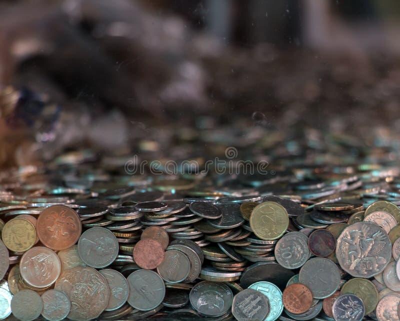 Många mynt från olika länder royaltyfri bild