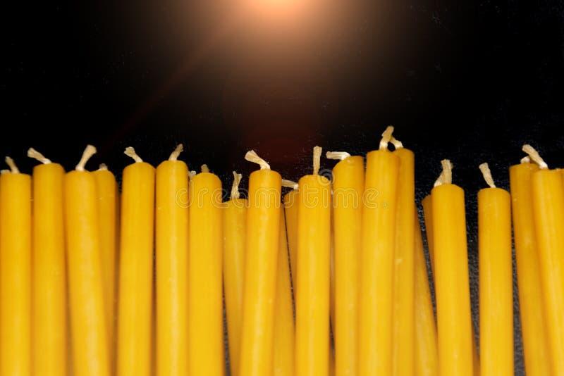 Många naturliga tunna gula vaxstearinljus ligger på svart bakgrund royaltyfria foton