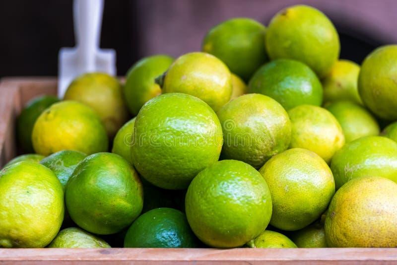 Många ny gräsplangulinglimefrukt på trähinken, limefruktskörd, arkivfoto