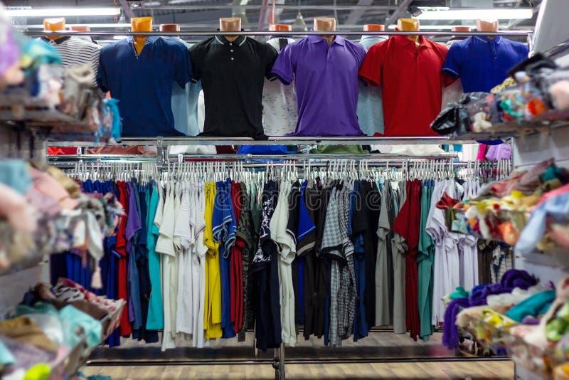 Många olik färgrik kläder på en hängande kugge i detaljhandeln shoppar lagret arkivfoto