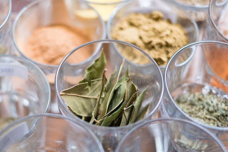 Många olika kryddor i exponeringsglas på tabellen arkivbilder