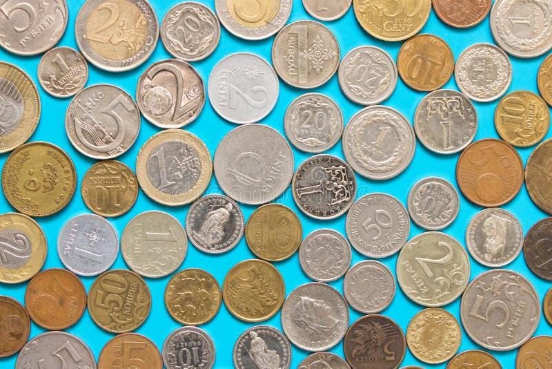 Många olika mynt på blå bakgrund Begreppet av besparingen fotografering för bildbyråer