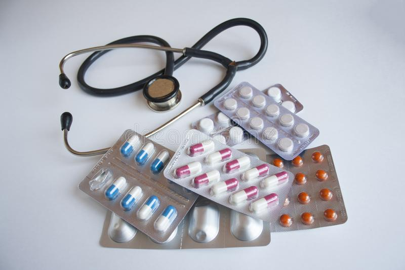 Många olika piller och en stetoskop royaltyfri foto