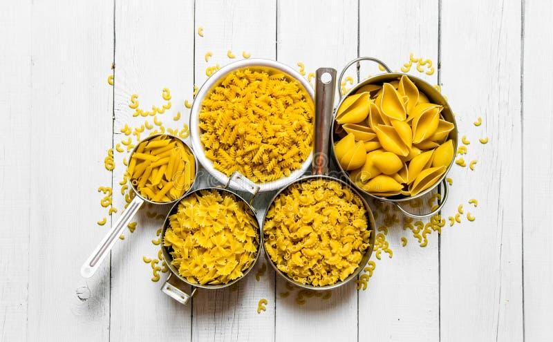 Många olika typer av torr pasta i krukan royaltyfria foton