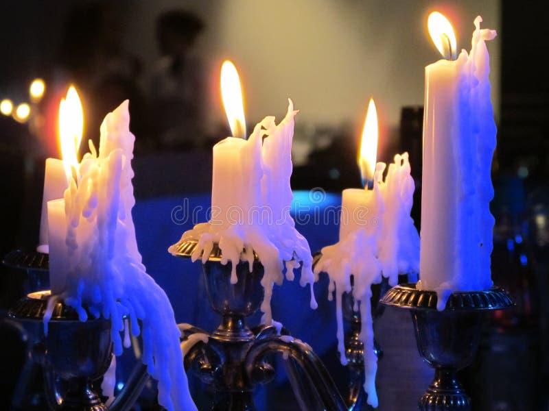Många paraffinstearinljus som bränner på en ljusstake arkivfoto