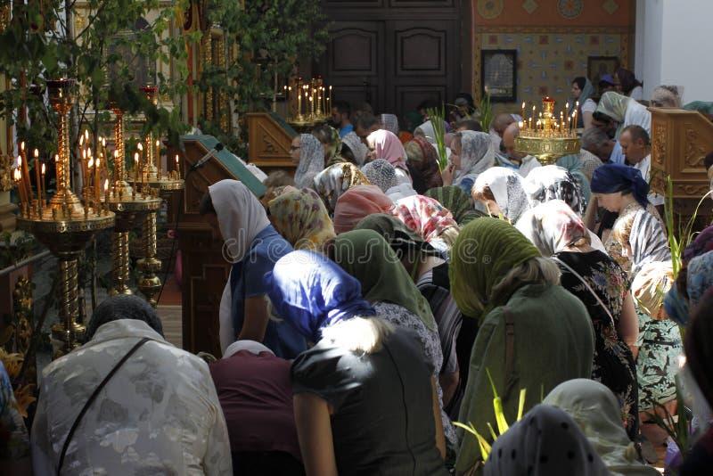 Många personer i kyrkan Folket ber på deras knä arkivbild