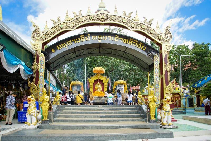 Många personer kommer att be på den guld- munkstatyn royaltyfri foto