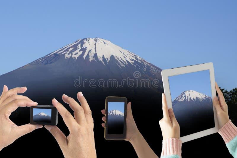 Många personer lyfter händer tar upp till fotoet av Mount Fuji vid smart D arkivfoton