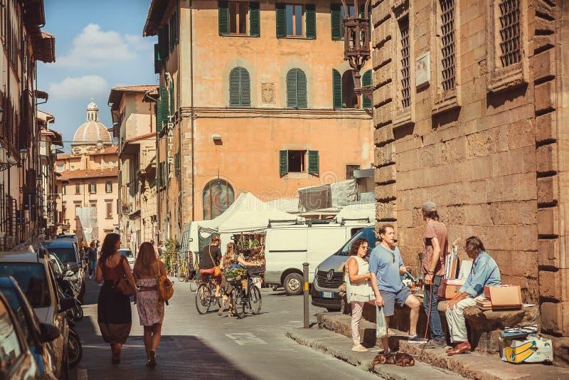 Många personer med vänner som går på historiska smala gator av den forntida Tuscany staden arkivfoton