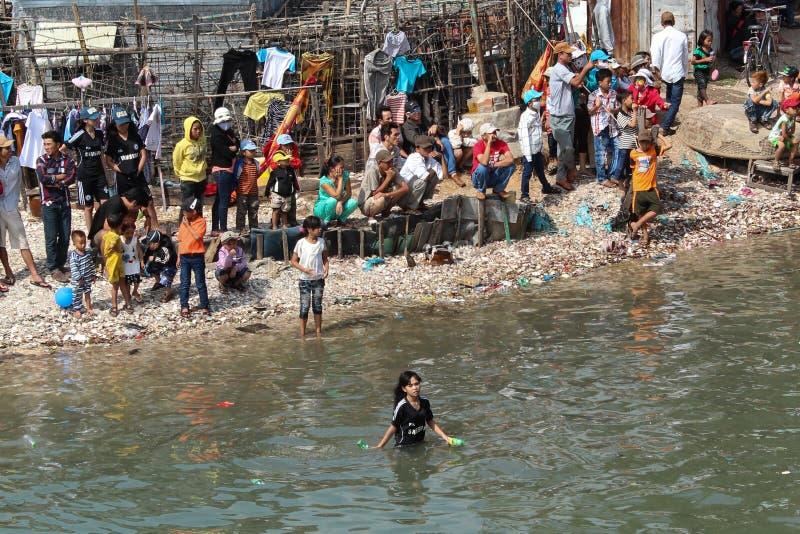 Många personer på strandkant och i vatten som ser i riktning av tr arkivbild