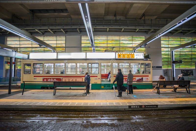 Många personer som använder den Centram spårvagnen i den Toyama stationen på natten royaltyfria bilder