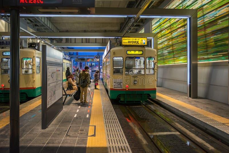 Många personer som använder den Centram spårvagnen i den Toyama stationen på natten royaltyfri fotografi