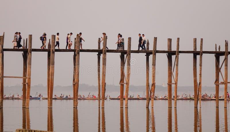 Många personer som går på bron i Mandalay, Myanmar royaltyfri foto