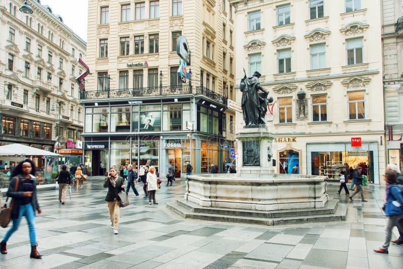 Många personer som går på den centrala delen av österrikisk huvudstad med gamla och moderna byggnader royaltyfria foton