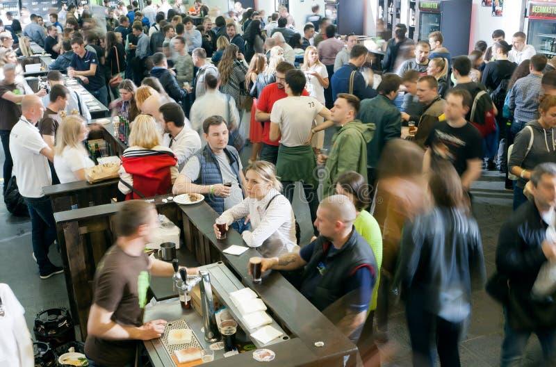 Många personer som smakar slag av öl i den enorma korridoren av stången arkivfoto