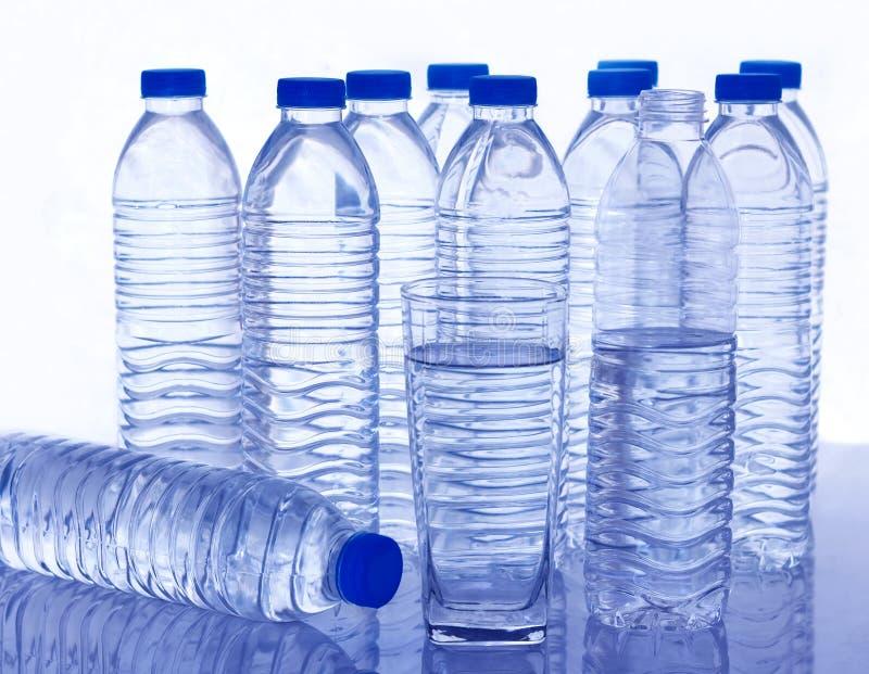 Många plast- vattenflaskor och ett exponeringsglas av vatten på tabellen arkivfoto