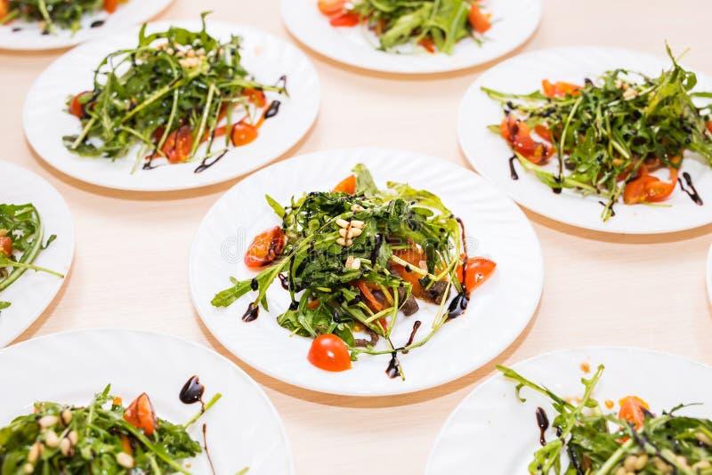 Många plattor med ny sallad med för tomater, tokig och blandad gräsplanarugula för höna, mesclun, mache på tabellen Sunt royaltyfria foton