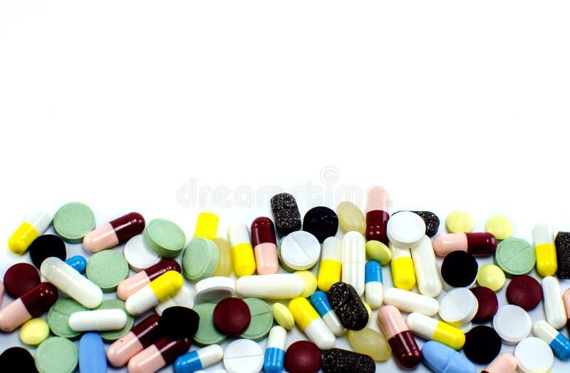Många preventivpillerar av olika färger på en vit bakgrund royaltyfria bilder