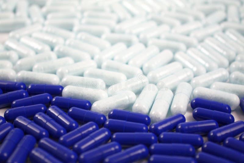Många preventivpillerar och minnestavlor i blått och vit färgar Medicinsk bakgrund för apotek Slut upp av många droger royaltyfria foton