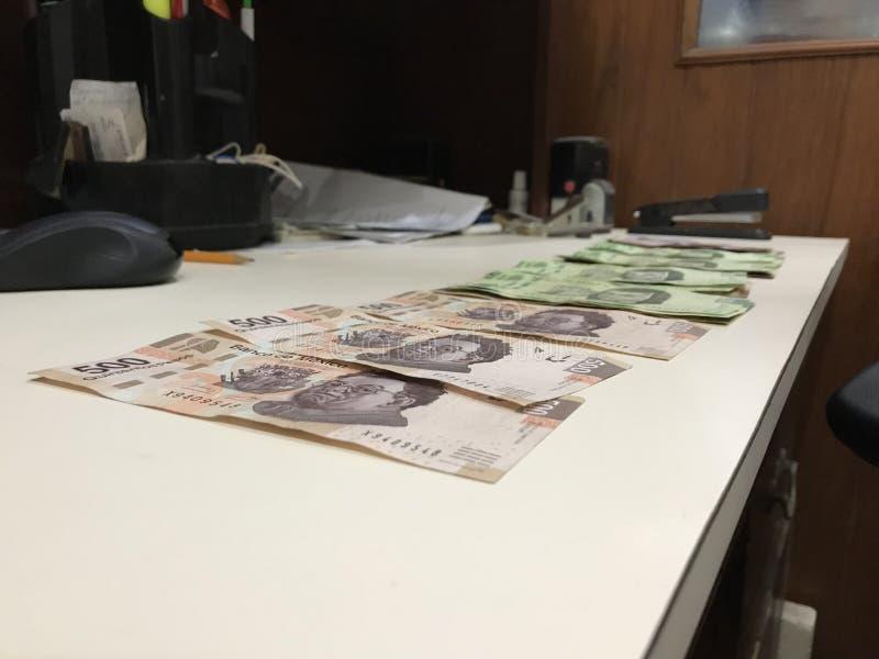 Många räkningar för mexikanska pesos fördelade och fördelade på ett beige kulört skrivbord arkivfoto