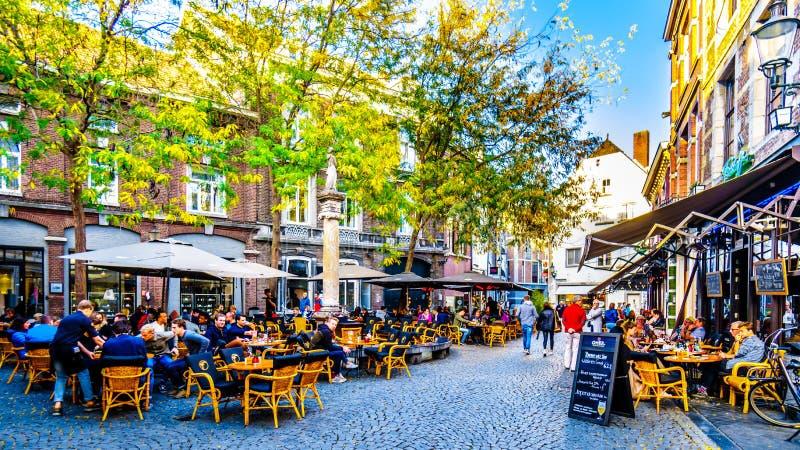 Många restaurang och barterrasser och uteplatser som ska hängas ut med vänner i mitten av den historiska staden av Maastricht royaltyfri foto