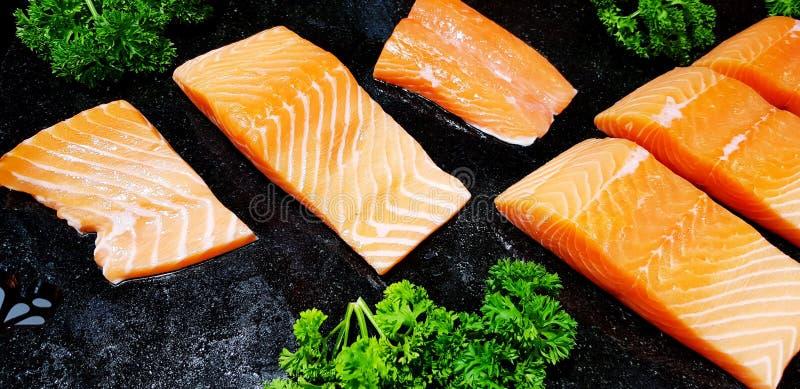 Många skivade den nya laxfisken eller sashimien med grönsaken på det svarta magasinet i matmarknad arkivfoton