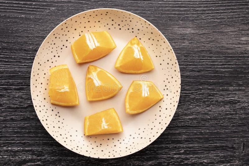 Många skivor av apelsinen på en svart trätabell i en brun prickig platta arkivfoton