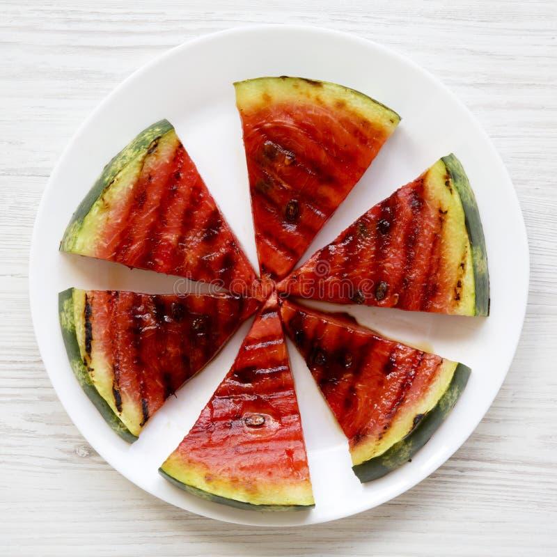 Många skivor av den nya mogna grillade vattenmelon på en vit rund platta över vit träyttersida, bästa sikt Sund sommarfrukt arkivbild
