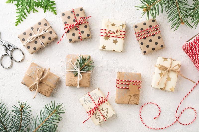 Många slogg in julgåvaaskar som bagare tvinnar & granen på den vita tabellen arkivbilder