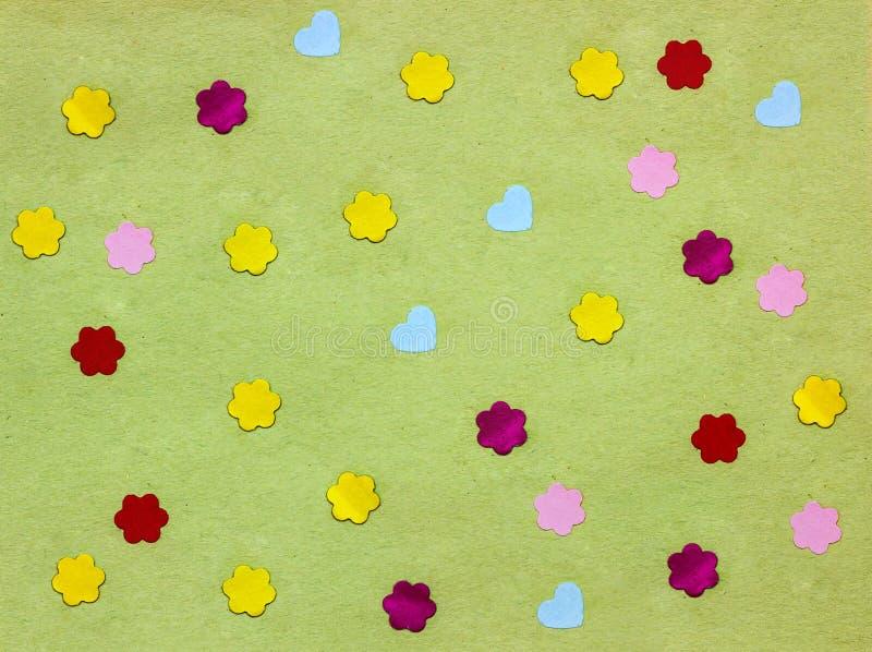 Många små pappers- hjärtor och blommor på grön bakgrund royaltyfria foton
