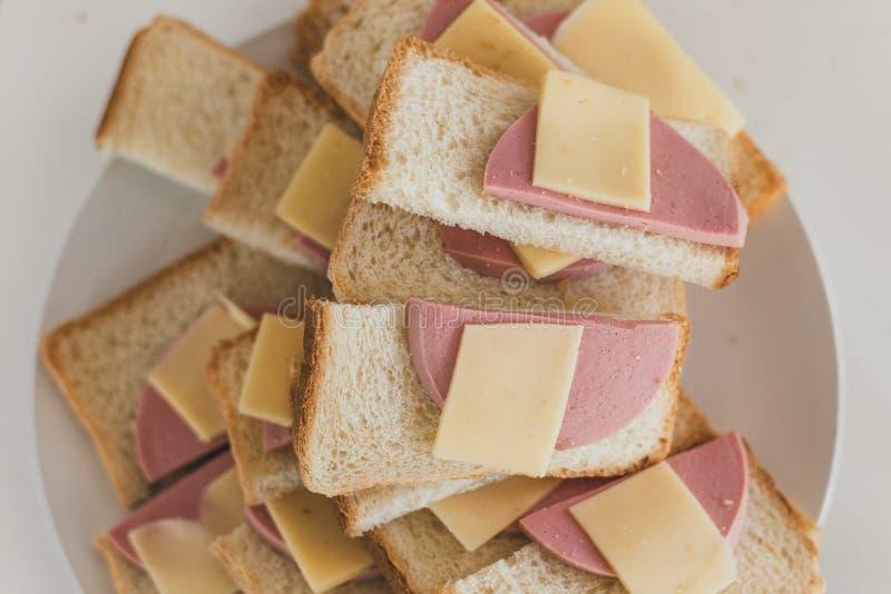 Många smörgåsar med korven och ost på en platta Doktorskorv på stycken av bröd Snabbt mellanmål för företaget arkivfoto